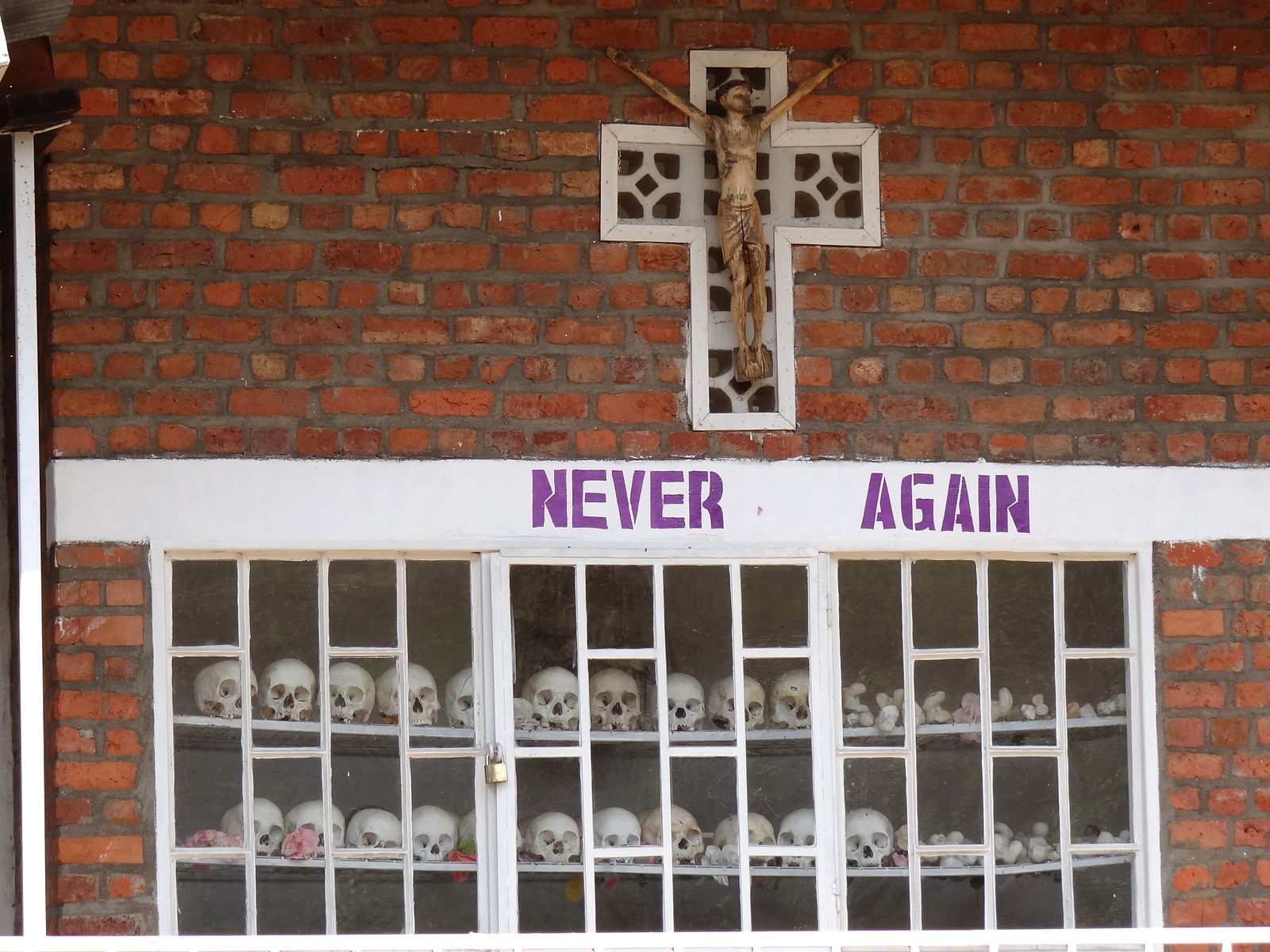 Never_Again_-_With_Display_of_Skulls_of_Victims_-_Courtyard_of_Genocide_Memorial_Church_-_Karongi-Kibuye_-_Western_Rwanda_-_01.jpg